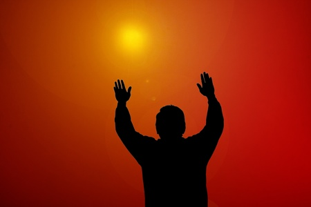 Sunset beam shining on man with hands up