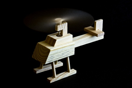 Wooden toy helicopter with spinning propeller on black background
