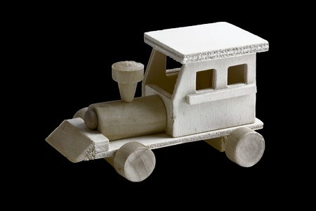 Wooden toy train with wheels on black background