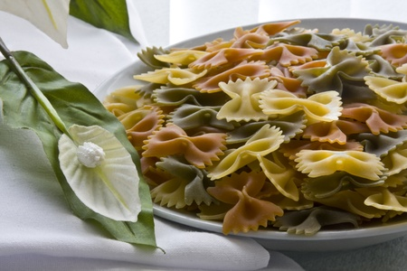 Tricolor farfalle pasta uncooked with flower, bowl and napkin