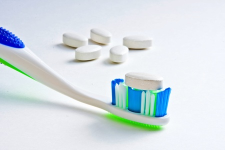 Calcium tablet resting on toothbrush bristles with other tablets in background Imagens