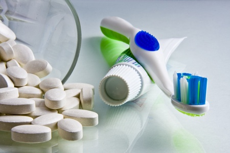 Calcium tablets spilled from glass with toothpaste and toothbrush beside them