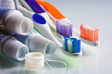Toothpaste tubes with various colored  toothbrushes and floss