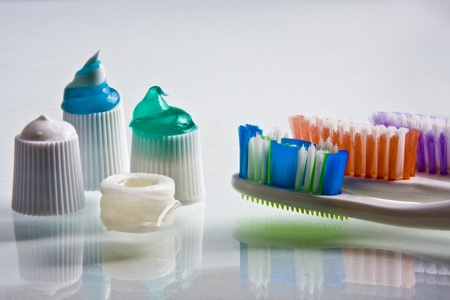 Colorful toothpaste squeezed onto their caps with toothbrushes and floss