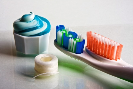 Toothpaste squeezed from tube onto cap with toothbrushes and floss
