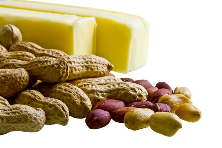 Closeup of peanuts in and out of shell with bars of butter on white background Imagens