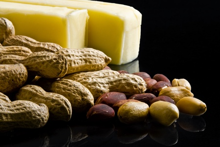 Closeup of peanuts in and out of shell with bars of butter on black background