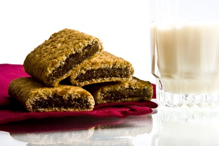 Wheat fig bars on red cloth napkin with glass of milk on white background Imagens