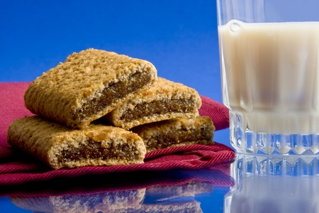 Wheat fig bars on red cloth napkin with glass of milk on blue background Imagens