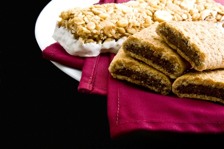 Wheat fig bars with nutty health bar on red cloth napkin and plate on black background