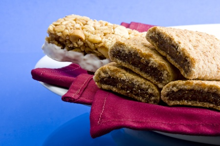 Wheat fig bars with nutty health bar on red cloth napkin and plate on blue background