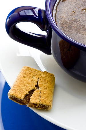 Wheat fig bar with coffee on white saucer