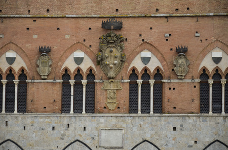 Detail of coats of arms on the facade of the town hall of Siena Stock Photo