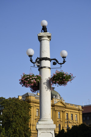 Characteristic lamppost festooned with flowers Stock Photo