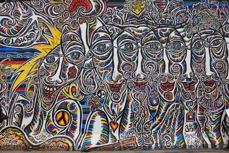 mauer: BERLIN, GERMANY --4 April 2011-- Artistic graffiti paintings, called the East Side Gallery, line a 1.3 km long section of the Berlin Wall Berliner Mauer near the river Spree.