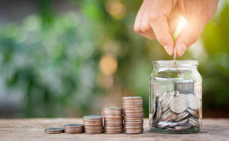 Hand putting coins in the jar on wooden table. The concept of saving money, finance, business and investment is growing in the future.