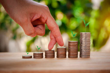 Male hand stacking coins with tree for the second step like growing for the future, education, home, loan and child on bokeh background.