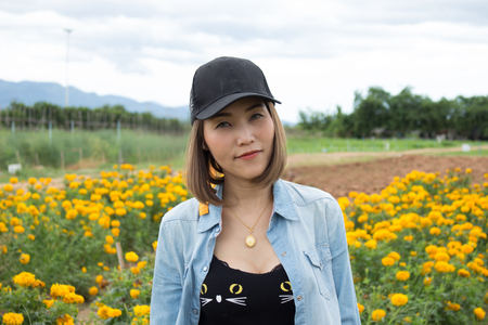 A woman standing in the middle of a field of marigolds Фото со стока
