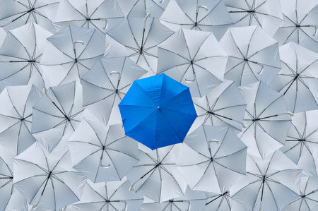 A normal blue umbrella is different from the overturn grey umbrellas, Being different concepts, Business concept, Leader, Blue umbrella can protect rain, grey umbrellas cant protect rain, Top view.