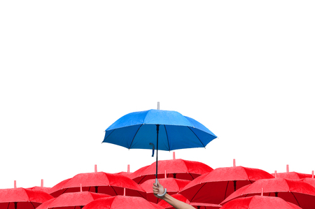 best protection: The difference to step up to leadership in business. hand of man holding a blue umbrella over many red umbrellas. raining. side view. Stock Photo