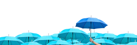 The difference to step up to leadership in business.blue umbrella among sky umbrellas. hand of man holding a blue umbrella over many umbrellas in raining. side view.