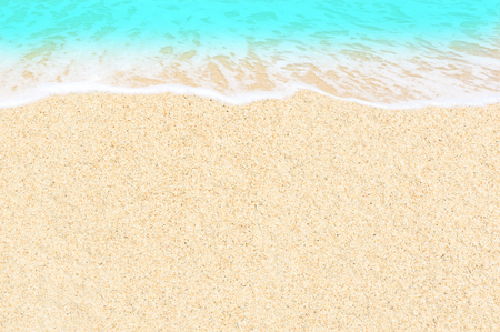 The wave of blue ocean on sandy beach for background. sand texture and water