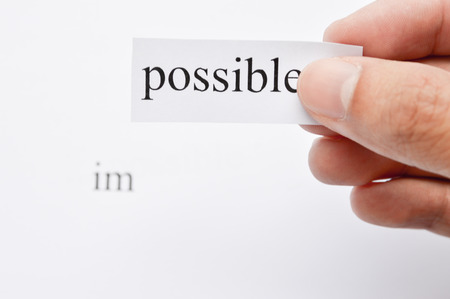 printout: Possible Concept. Changing The Word Impossible to Possible. Seperate word im and possible.  hand holding possible words. word im on white paper. Focus at text or words.