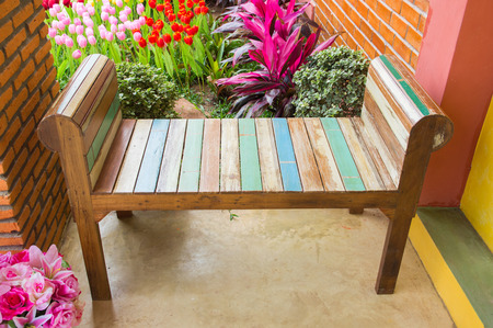 Wooden bench. A seat made from wood. resting seat. seating with flowers.
