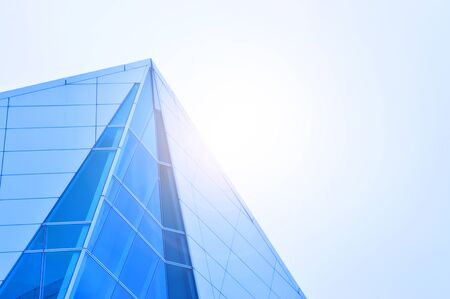 Widok z boku na biuro firmy wieżowiec z błękitne niebo, budynek firmy w mieście z lekkim polotem.