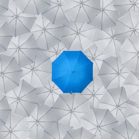 Diferente, único y sobresaliendo del paraguas azul, vista superior, éxito en el concepto empresarial.