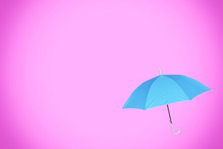 Pastel pink background with blue umbrella. Abstract wallpaper with copy space.
