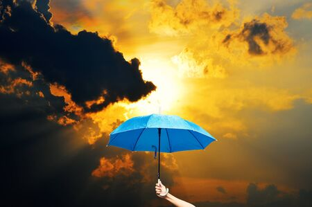 hand holding a blue umbrella in sun and clouds all day