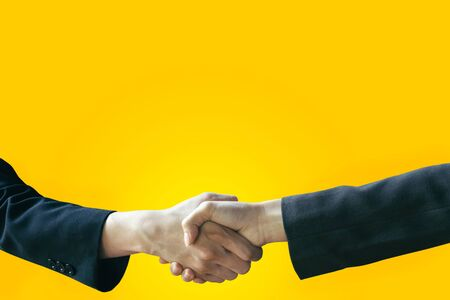 Business handshake on yellow background with copy space for text