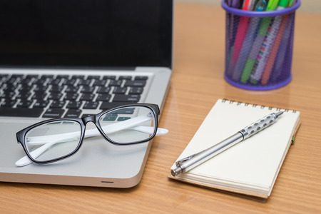 equities: Blank business laptop, pen, note and glasses on wooden table Stock Photo