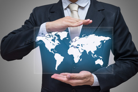 hand holding world: Businessman standing posture hand holding world map isolated on gray background Stock Photo