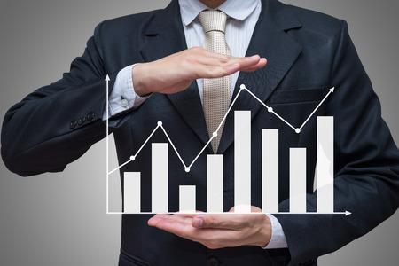 Zakenman staande houding hand houden grafiek financiën geïsoleerd op grijze achtergrond Stockfoto