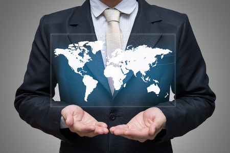Businessman standing posture hand holding world map isolated on gray background Stock Photo