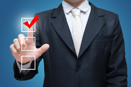 checklist: Businessman touch checking mark checklist marker Isolated on blue background