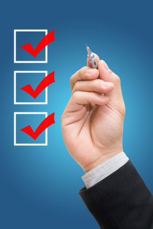 Businessman checking mark checklist marker Isolated on blue background 스톡 콘텐츠