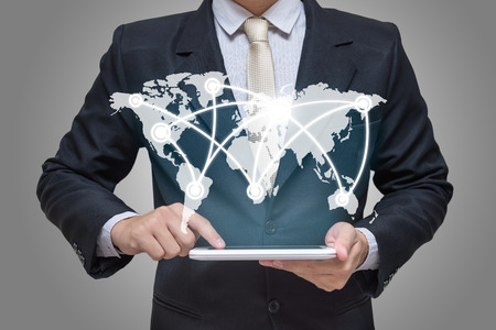 comercio: Empresario de la mano que sostiene la tablilla de marketing global sobre fondo gris