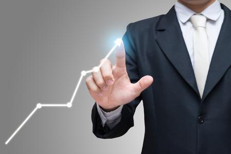 Homme d'affaires posture debout toucher la main de la finance graphique isolé sur fond gris Banque d'images - 47270112