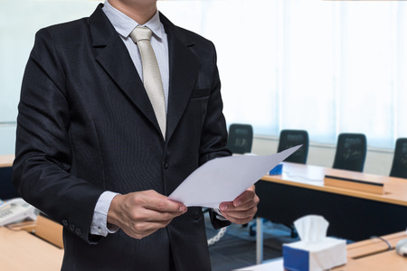 Businessman standing hand holding paper on meeting room background