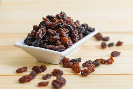 Raisins in saucer on wooden table, close-up