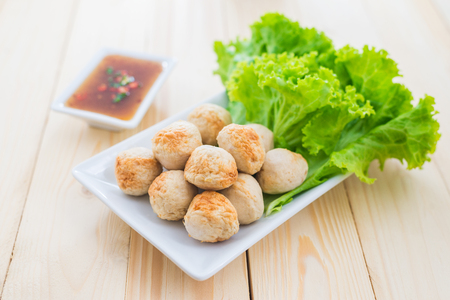 Grill pork balls with sweet spicy sauce on wooden table