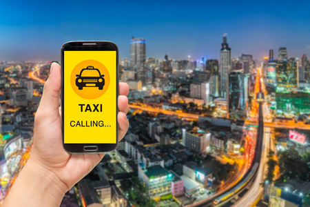 Calling Taxi message on a mobile phone screen. Hand holding smart phone on city background