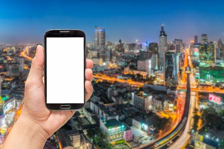 Une main tenant écran blanc téléphone intelligent avec la ville de fond Banque d'images - 59796489