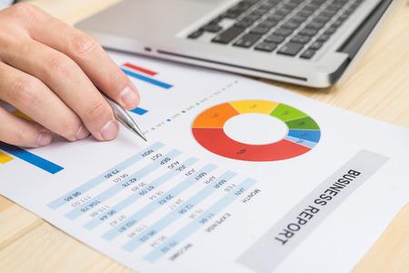 Homme d'affaires analysant le rapport financier avec un ordinateur portable. Comptabilité Banque d'images - 60851280