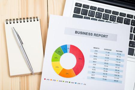 Rapport financier avec un ordinateur portable sur la table en bois. Comptabilité Banque d'images - 60851591