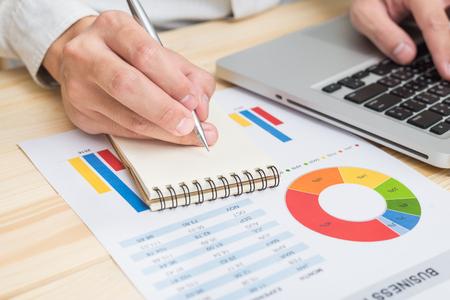 Homme d'affaires analysant le rapport financier avec un ordinateur portable. Comptabilité Banque d'images - 60851631