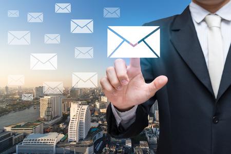 Homme d'affaires main touchant des messages ou des lettres sur fond de ville Banque d'images - 61778793